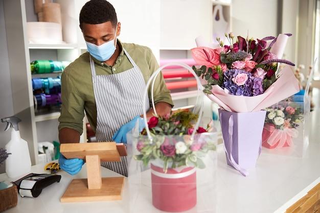 Sprzedawczyni kwiaciarni w rękawiczkach i maseczce obsługująca tablet leżący na drewnianym stojaku