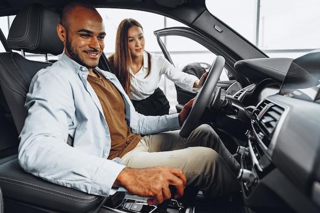 Sprzedawczyni młoda atrakcyjna kobieta w salonie samochodowym pokazując samochód jej męskiego klienta