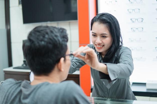 Sprzedawczyni pomaga mężczyźnie założyć okulary, gdy siedzi i przymierza okulary u optyka