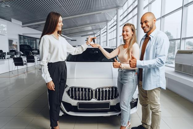 Sprzedawczyni samochodów w salonie samochodowym rozmawiająca z klientami kupującymi