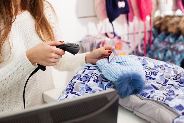 Sprzedawczyni skanuje czapkę zimową w sklepie