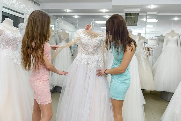 Sprzedawczyni w salonie ślubnym, pomagając młodej narzeczonej