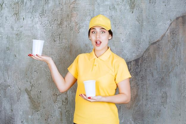 Sprzedawczyni w żółtym mundurku trzymająca dwie plastikowe kubki z napojami i podająca jedną drugiej osobie