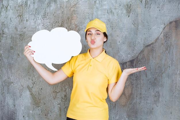 Sprzedawczyni w żółtym mundurze trzyma tablicę informacyjną w kształcie chmury i pokazuje pozytywne znaki.