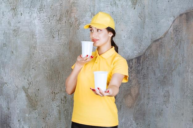 Sprzedawczyni w żółtym mundurze trzymająca dwie plastikowe kubki z napojami i podająca jedną drugiej osobie.