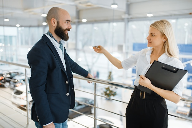 Sprzedawczyni zaprasza mężczyznę do prezentacji w salonie samochodowym. klient i sprzedawczyni w salonie samochodowym, mężczyzna kupujący transport, firma dealera samochodowego