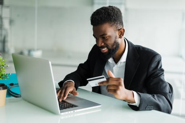Sprzedaż bankowości internetowej. pomyślny afrykański biznesmena obsiadanie przy laptopem i trzymający w ręku kartę kredytową, dopóki biznesmen robi rozkazom przez internet