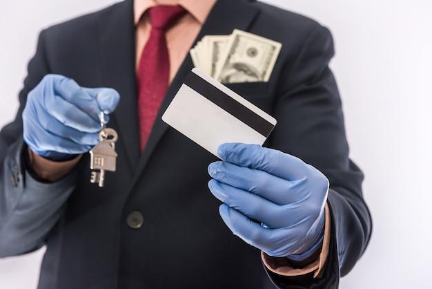 Sprzedaż bezpieczeństwa lub wynajem domu człowiek w rękawicach medycznych trzyma klucz do domu i dolara. ncov-2019