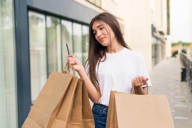 Sprzedaż i turystyka, koncepcja szczęśliwych ludzi - piękna kobieta trzyma kartę kredytową z torby na zakupy w ctiy
