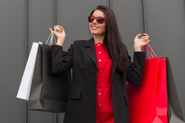 Sprzedaż kobieta czarny piątek trzymając różne torby na zakupy