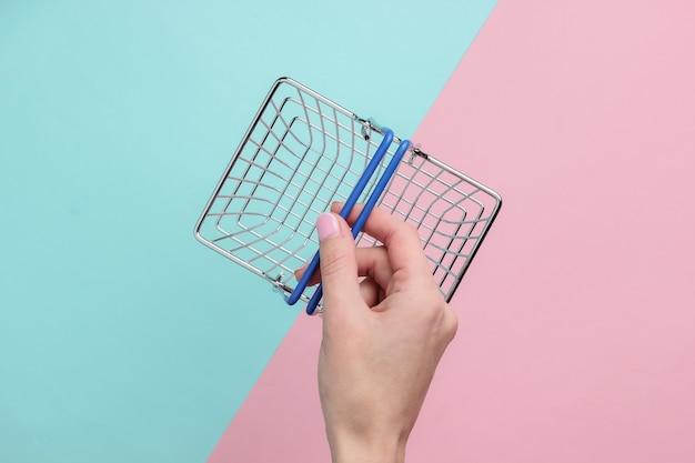 Sprzedaż koncepcji zakupów online dłoń trzymająca mini koszyk na pastelowym różowo-niebieskim tle