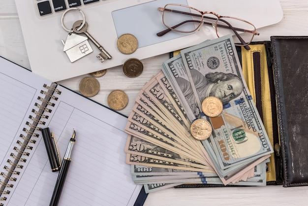 Sprzedaż lub wynajem kluczy do domu koncepcji z dolarowych i laptopa, oszczędzając