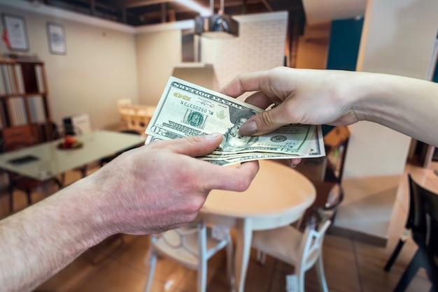 Sprzedaż mebli w sklepie, kupujący płaci kasjerowi za swój towar. dolar w rękach