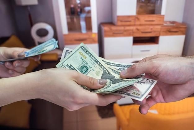 Sprzedaż mebli w sklepie, kupujący płaci kasjerowi za swój towar. dolara w rękach