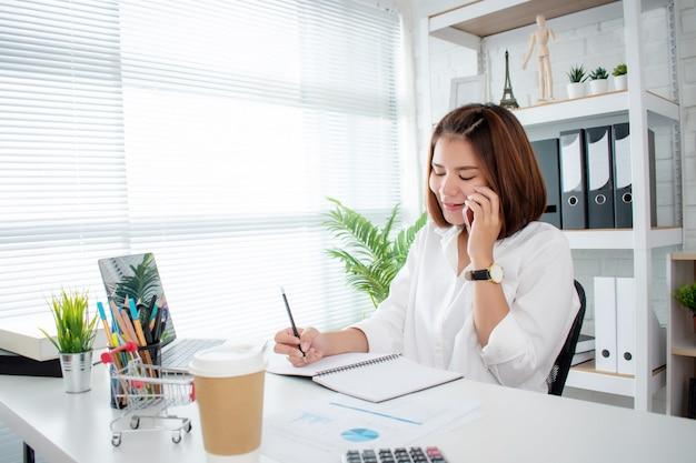 Sprzedaż online odpowiada na pytania klientów za pośrednictwem smartfona, prowadząc interesy w jej domu. z notatkami na biurku