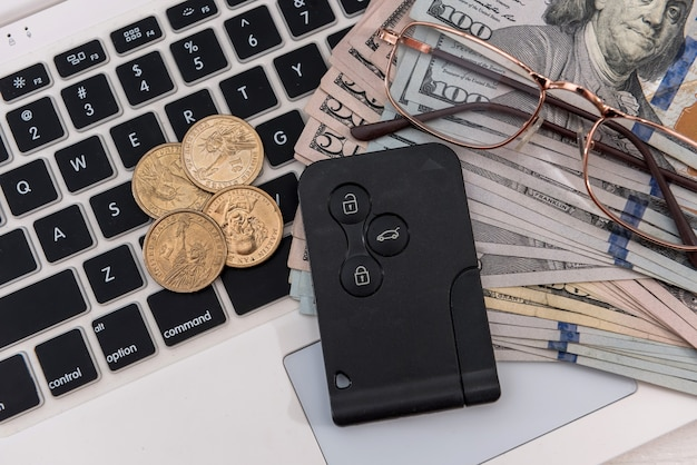 Sprzedaż online zakup kluczyki do samochodu koncepcyjne z banknotami dolarowymi nad zbliżeniem klawiatury laptopa