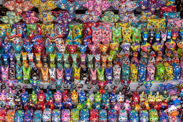 Sprzedaż pamiątek - śmieszne ręcznie robione drewniane zwierzęta na targu ulicznym. jasne kolorowe zabawki dla dzieci i dekoracja wnętrz. ubud, wyspa bali, indonezja. ścieśniać