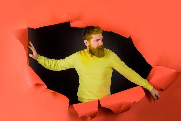 Sprzedaż reklamowa brodaty mężczyzna przez papierową przestrzeń do kopiowania dla mężczyzny reklamowego patrzącego przez otwór w