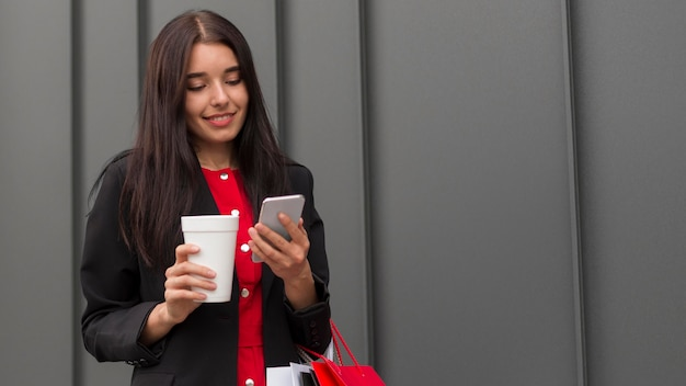 Sprzedaż w czarny piątek kobieta z kawą i telefonem komórkowym