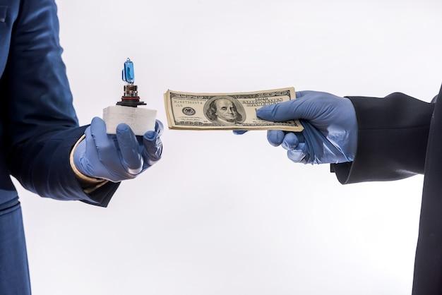 Sprzedaż w warunkach kwarantanny koronawirusa ręce trzymające żarówki samochodowe i izolowane dolary. kupowanie koncepcji samochodu