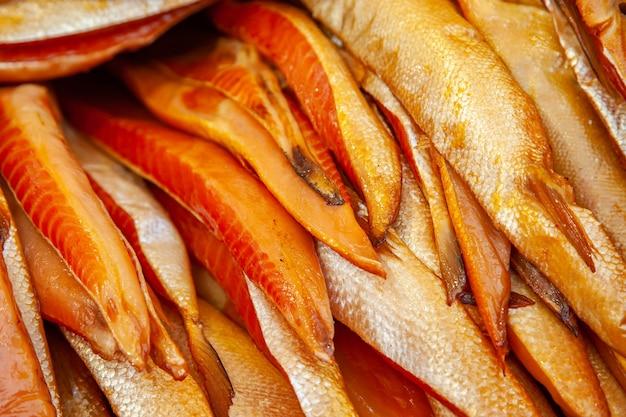 Sprzedaż wędzonej ryby kamczackiej. dalekowschodnie owoce morza, naturalne wędzone ryby - boczki łososia chinook na miejskim jarmarku bożonarodzeniowym.
