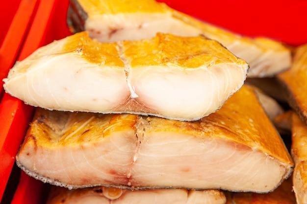 Sprzedaż wędzonej ryby kamczackiej. owoce morza dalekiego wschodu, naturalna ryba wędzona - łosoś inconnu na miejskim jarmarku bożonarodzeniowym.