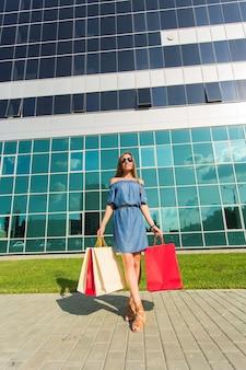 Sprzedaż, zakupy i koncepcja szczęśliwych ludzi - piękna kobieta z torby na zakupy spaceru na ulicy.