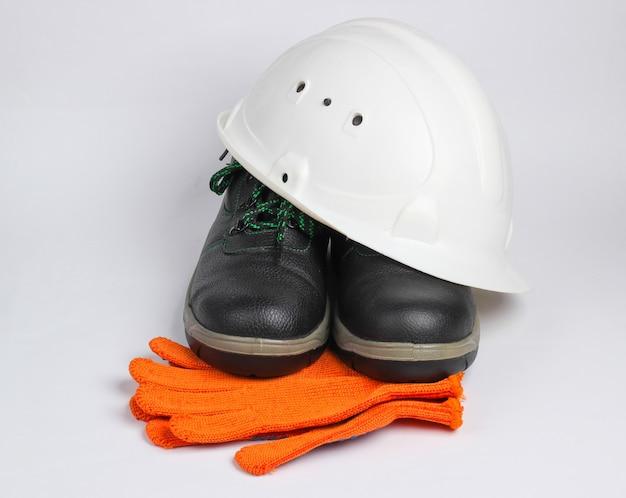 Sprzęt bezpieczeństwa na białym tle. kask budowlany, skórzane buty robocze, rękawiczki na białym tle.