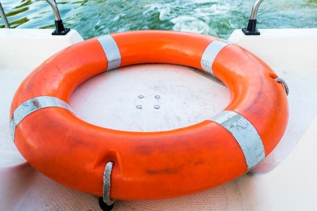 Sprzęt bezpieczeństwa, ratownik lub koło ratunkowe. osobiste urządzenie unoszące na wodzie, aby zapobiec utonięciu. pomarańczowy ratownik na pokładzie statku.