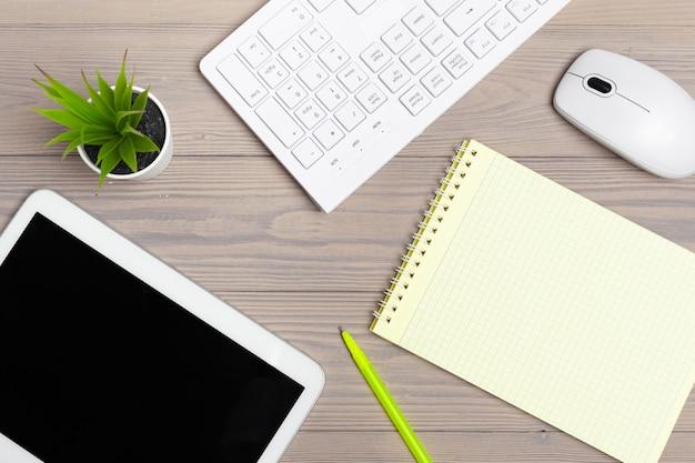 Sprzęt biurowy, taki jak klawiatura komputerowa i inne materiały eksploatacyjne na drewnianym stole