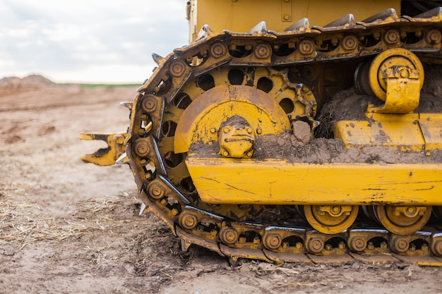 Sprzęt budowlany gąsienicowy w kolorze żółtym