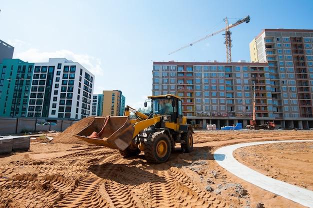 Sprzęt budowlany wyrównuje grunt pod ułożenie nowych płyt chodnikowych w parku w okresie letnim