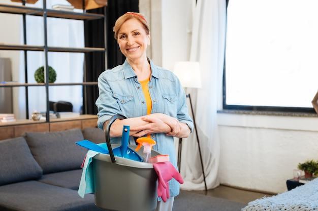 Sprzęt czyszczący. pozytywna, ładna kobieta z szerokim uśmiechem stojąca na środku mieszkania i przygotowująca się do sprzątania
