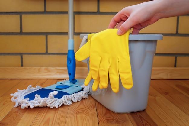 Sprzęt do czyszczenia. mop, plastikowe wiadro i gumowe rękawiczki, ręka sięga po rękawicę