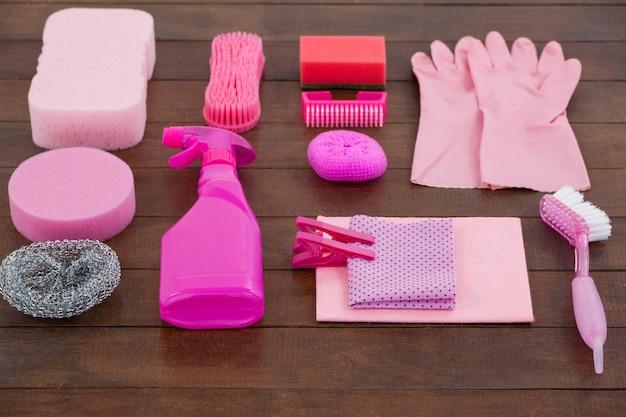 Sprzęt do czyszczenia w kolorze różowym ułożony na drewnianej podłodze