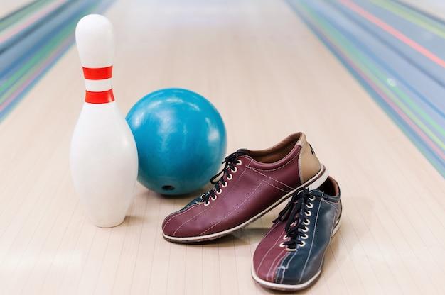 Sprzęt do gry w kręgle . zbliżenie na buty do kręgli, niebieską piłkę i szpilkę leżące na kręgielni