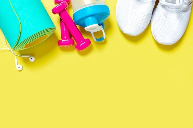 Sprzęt fitness flat lay hantle, trampki, butelka na wodę i mata do jogi