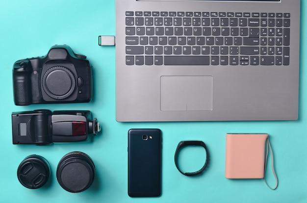 Sprzęt fotograf, laptop, smartfon, inteligentny zegarek, power bank, na niebieskim tle. koncepcja niezależna, gadżety do pracy, przedmioty, widok z góry, leżał płasko