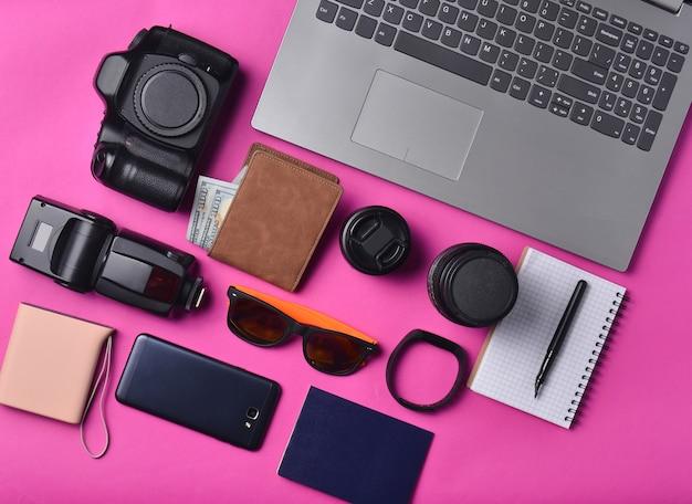 Sprzęt fotograf, laptop, torebka z dolarów, smartfon, zegarek, paszport, power bank, na żółtym tle. koncepcja niezależna, gadżety do pracy i podróży, przedmioty, widok z góry, płaskie układanie