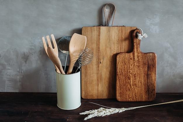 Sprzęt kuchenny na drewnianym blacie, przy szarej, teksturowanej ścianie. suche kłoski