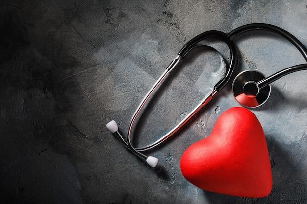 Sprzęt medyczny i obiekt w kształcie serca na stole z miejsca na kopię