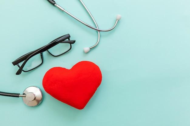 Sprzęt medyczny stetoskop lub fonendoskop okulary i czerwone serce na modnym pastelowym niebieskim tle. przyrząd dla lekarza. pojęcie ubezpieczenia na życie opieki zdrowotnej