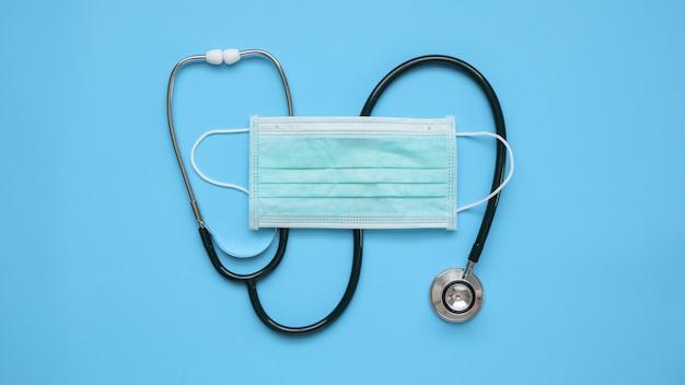 Sprzęt medyczny stetoskop z maską chirurgiczną. covid-19 koncepcja opieki zdrowotnej w zakresie zapobiegania koronawirusowi