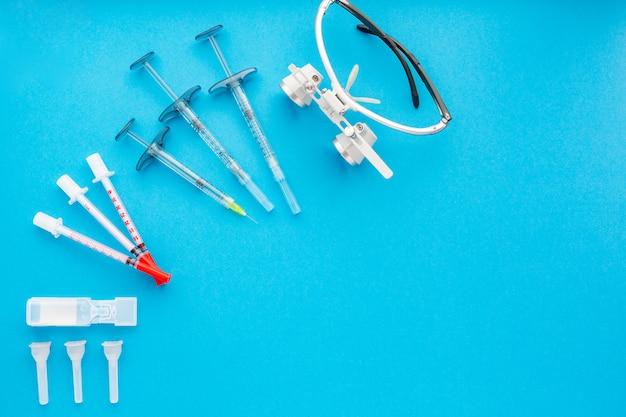 Sprzęt medyczny, w tym instrumenty chirurgiczne na niebieskim tle. widok z góry, kopiuj spase