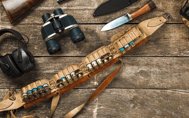 Sprzęt myśliwski na starym drewnianym tle, w tym lornetka z nożem karabinowym i naboje