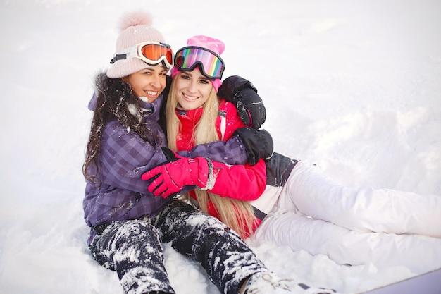 Sprzęt narciarski w rękach dziewczyn. jasne kolory odzieży narciarskiej. dziewczyny dobrze się razem bawią.