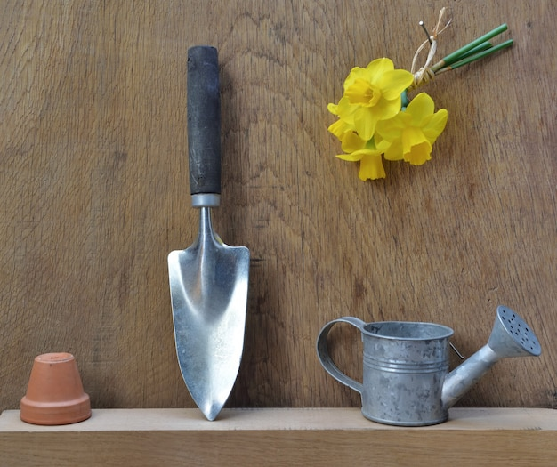 Sprzęt ogrodniczy ułożony na drewnianym stole z żonkilami