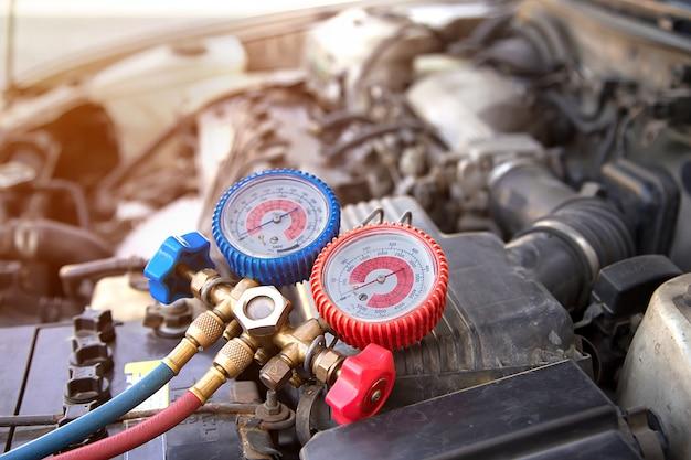 Sprzęt pomiarowy do kontroli napełniania klimatyzatorów samochodowych. koncepcje usługi naprawy samochodu i ubezpieczenia samochodu.