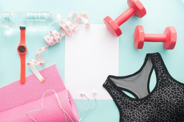 Sprzęt sportowy, fitness i jogi z biustonoszem sportowym i białym czystym papierem