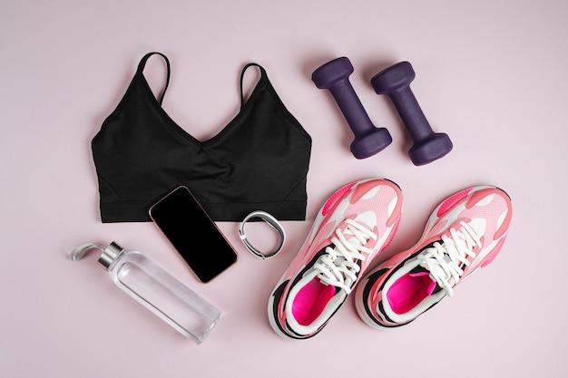 Sprzęt sportowy fitness i trampki na różowym tle.